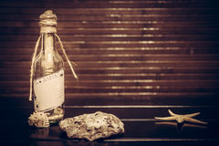 Vintage tropical background with message in bottle and copy space. Message in a bottle with copy space on tropical wooden background with sea shells Stock Images