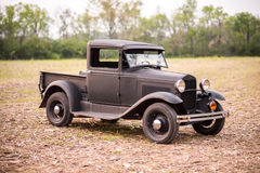 Vintage Truck. A vintage truck in a field with a forest in the background Royalty Free Stock Photo
