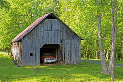 Vintage truck sits inside an old wooden barn. Stock Photo