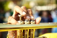 Vintage trumpet in gentle. Brass vintage trumpet in gentle illumination. Jazzman holds the musical instrument in his hands while pushing on buttons Royalty Free Stock Images