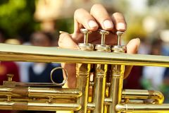 Vintage trumpet in gentle. Brass vintage trumpet in gentle illumination. Jazzman holds the musical instrument in his hands while pushing on buttons Stock Photo