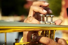 Vintage trumpet in gentle. Brass vintage trumpet in gentle illumination. Jazzman holds the musical instrument in his hands while pushing on buttons Royalty Free Stock Image