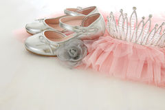 Vintage tulle pink chiffon dress, crown and silver shoes on wooden white floor royalty free stock photography