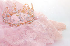 Vintage tulle pink chiffon dress and diamond tiara on wooden white table. Wedding and girl& x27;s party concept.  royalty free stock photography