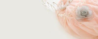Vintage tulle pink chiffon dress and diamond tiara on wooden white table. Wedding and girl& x27;s party concept. Vintage tulle pink chiffon dress and diamond Royalty Free Stock Photos