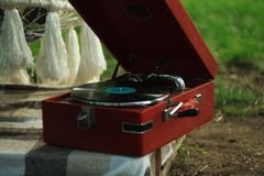 Vintage turntable vinyl record player on nature background. Wooden plinth. Retro audio equipment. stock image
