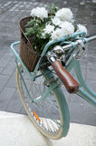 Vintage Turquoise bicycle with a tray of white flowers Stock Photo