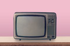 Vintage TV box on wooden table and pink pastel color background. royalty free stock photos