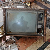 Vintage tv set. Vintage broken television tv set with wooden frame on dirty floor Royalty Free Stock Images