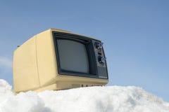 Vintage TV on snow. Portable vintage TV on a ski hill Royalty Free Stock Photos