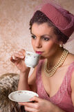 Vintage twenties lady. Attractive vintage 1920s lady with flapper dress and matching hat drinking tea stock image