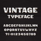 Vintage typeface. Retro alphabet font. Type letters and numbers on a rough wooden background. Vector font for your headers or any typography design Stock Image