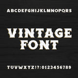 Vintage typeface. Retro distressed alphabet font on a wooden background.  Stock Images