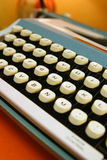Vintage Typewriter. An old blue typewriter sitting on an orange colored table Stock Photo