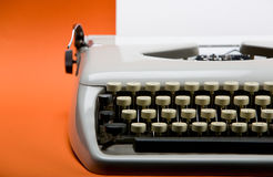 Vintage typewriter. Old style typewriter with inserted blank paper over orange background Royalty Free Stock Images