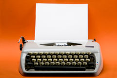 Vintage typewriter. Old style typewriter with inserted blank paper over orange background Stock Photos