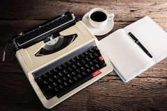 Vintage typewriter and a blank notebook , pen and coffee cup Stock Image