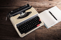 Vintage typewriter and a blank notebook and pen Royalty Free Stock Photo