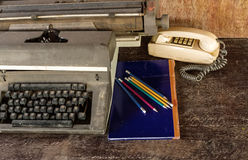 Vintage typewriter ,blue  book,  ,pencil and old telephone on ol Royalty Free Stock Photo
