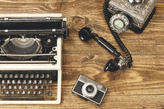 Vintage typewriter,camera and an old telephone on wooden table a Royalty Free Stock Images