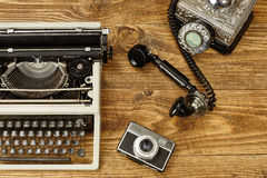 Vintage typewriter,camera and an old telephone on wooden table a Royalty Free Stock Photography