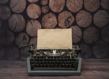 Vintage typewriter with a clean yellowed old sheet of paper. On a background of a tree of rustic logs. for the design of your text design Stock Image