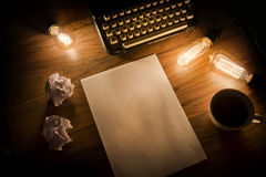 Vintage Typewriter Desk. A Vintage Typewriter on a wooden table with lightbulbs and writing paper Royalty Free Stock Photos