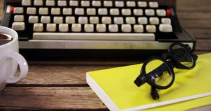 Vintage typewriter, diary, black coffee and spectacles on wooden table 4k stock footage