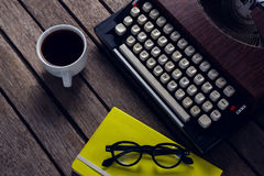 Vintage typewriter, diary, black coffee and spectacles on wooden table. Overhead of vintage typewriter, diary, black coffee and spectacles on wooden table Royalty Free Stock Photo