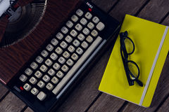 Vintage typewriter, diary and spectacles on wooden table. Overhead of vintage typewriter, diary and spectacles on wooden table Royalty Free Stock Image