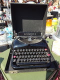 A Vintage Typewriter Found at a Flea Market. A vintage Remington 5 typewriter in its original black case on display at a local flea market stock photo
