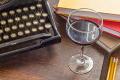 Vintage Typewriter Glass of Wine. Old vintage typewriter with glass of wine pencils and books in this retro creative writing and relazation themed desk top royalty free stock image