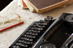 Vintage typewriter, glasses, pencils and note books. On linen tablecloth Stock Photo