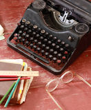 Vintage typewriter, glasses, pencils and note books. On red painted wood Royalty Free Stock Image