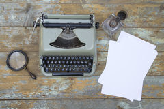 Vintage typewriter, inkwell, magnifier and the sheets of paper Royalty Free Stock Photo