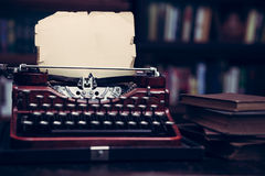 Vintage typewriter in a library. With barrister bookcases from 1920s era with vintage filtered effect Stock Photo