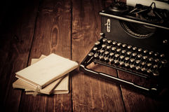 Vintage typewriter and old books stock images
