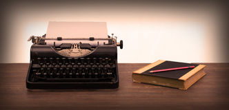 Vintage typewriter and old books. Touch-up in retro style Royalty Free Stock Photography