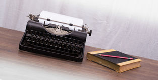 Vintage typewriter and old books Stock Photos
