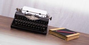 Vintage typewriter and old books Stock Photos