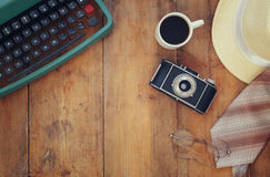 Vintage typewriter, old camera, glasses, cup of coffee. And fedora hat on wooden background. Top view Stock Images