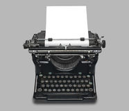 Vintage typewriter and paper, isolated. Old fashioned, vintage typewriter with a blank sheet of paper inserted, isolated with clipping path Royalty Free Stock Photos