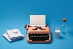 Composition with typewriter, books, glass and bottle. Vintage typewriter with a paper sheet on the blue background in the studio. Next to it there are few books Royalty Free Stock Image