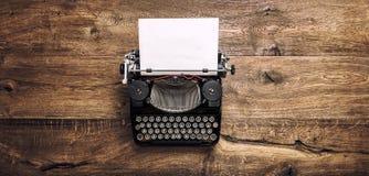 Vintage typewriter paper wooden background toned. Vintage typewriter with paper page on rustic wooden background. Toned photo stock image