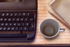 Vintage typewriter, pencil, paper and empty coffee cup Royalty Free Stock Photo