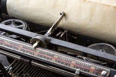 Vintage typewriter ribbon mechanism closeup. Vintage typewriter ribbon mechanism with inserted old paper closeup Royalty Free Stock Photo