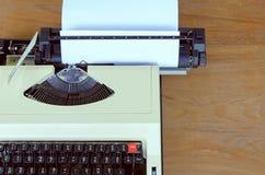 Vintage typewriter with white paper on wood background, retro to Stock Photos
