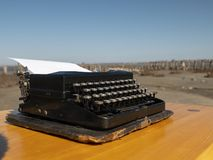 Vintage typewriter on a wooden table, handmade on a blue sky background royalty free stock photography