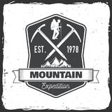 Vintage typography design with ice ax and mountain silhouette. Mountain expedition badge. Vector illustration. Concept for shirt or logo, print, stamp or tee Royalty Free Stock Image
