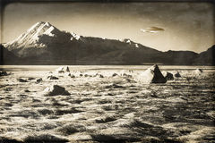 Vintage UFO in Alaska. UFO over an Alaskan beach with mountains processed with textures for a vintage look Stock Photo